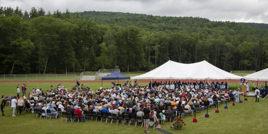 An elevated photo of a crowd on a football field waiting for a graduation ceremony