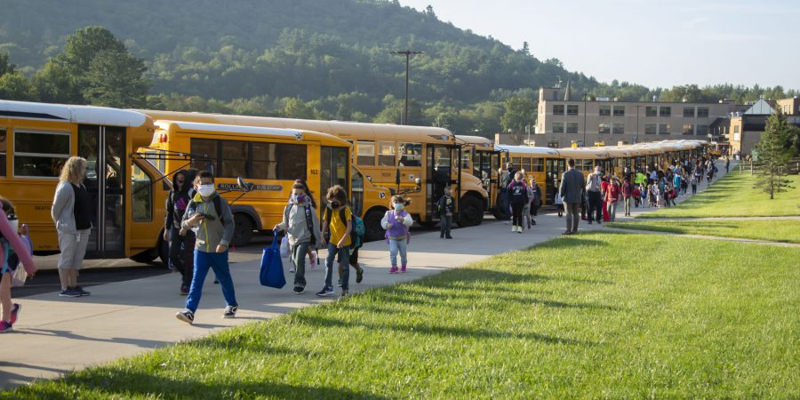 A line of school buses with student walking past on a sidewalk